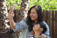 Mother and son posing for smartphone selfie in garden - ISF13245