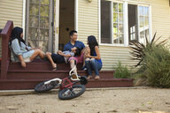 Family with boy relaxing on house steps - ISF13248
