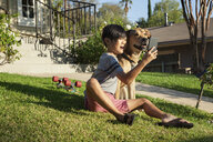 Boy posing for smartphone selfie with dog in garden - ISF13254