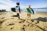 Couple running towards sea, carrying surfboards, rear view - ISF13356