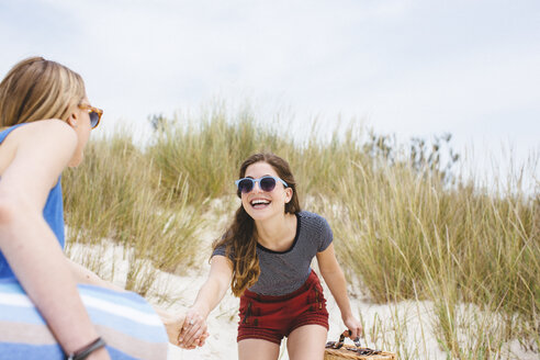 Two young female friends holding hands on sand dunes - ISF13368