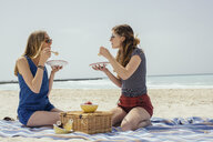 Two young female friends eating picnic on beach - ISF13383