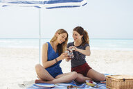 Two young female friends pouring picnic drinks on beach - ISF13386