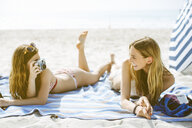 Two young female friends taking photographs whilst sunbathing on beach - ISF13395