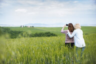 Two mature female friends photographing from wheatfield, Tuscany, Italy - ISF13464