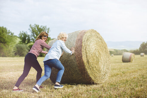 Two mature female friends pretending to push straw bale, Tuscany, Italy - ISF13467