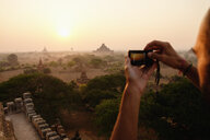 Man taking photograph of view, Bagan Archaeological Zone, Buddhist temples, Mandalay, Myanmar - ISF13518