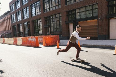 Cool mid adult male skateboarder skateboarding on city street, West Village, Manhattan, USA - ISF13551
