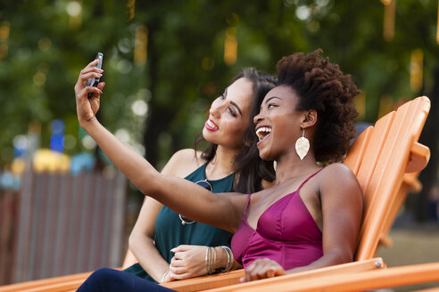 Young women taking selfie in deck chair - ISF13587