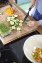 Woman slicing cucumber in kitchen - ISF13638