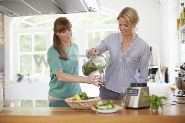 Women drinking green vegan smoothie in kitchen - ISF13650