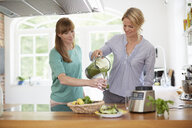 Women drinking green vegan smoothie in kitchen - ISF13650
