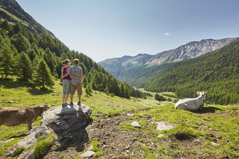 Rear view of young couple standing on boulder looking out to mountains, Val Senales, South Tyrol, Italy - ISF13683