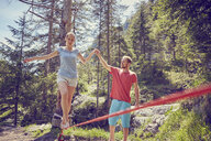 Woman balancing on rope with help from man, Ehrwald, Tyrol, Austria - ISF13740