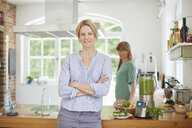 Women next to blender full of green vegan smoothie - ISF13821