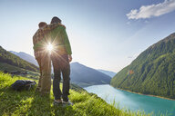 Young couple looking out over Vernagt reservoir and Finailhof farmhouse, Val Senales, South Tyrol, Italy - ISF13926