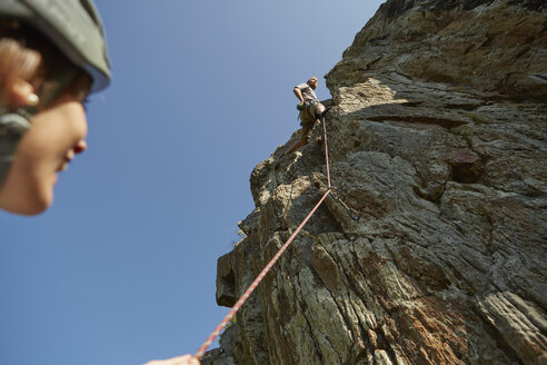 Low angle view of young rock climbing couple climbing rock formation, Val Senales, South Tyrol, Italy - ISF13929