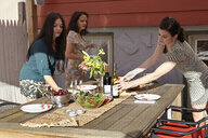 Three female friends preparing lunch on patio table - ISF14031