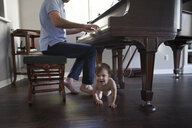 Father playing piano with baby boy crawling at feet - ISF14055