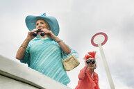 Senior women at races looking through binoculars - CUF33230