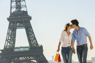 Young couple kissing near Eiffel Tower, Paris, France - CUF33239