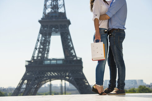 Young couple embracing in front of  Eiffel Tower, Paris, France - CUF33242
