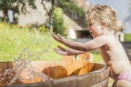 Female toddler splashing hands in water barrel - CUF33257