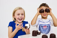 Studio shot of brother and sister with chocolate marshmallows - CUF33344