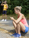 Young female runner sitting on sidewalk looking at cellphone - CUF33347