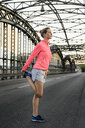 Young female runner stretching on bridge - CUF33377