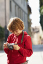 Young boy checking photographs on street, Province of Venice, Italy - CUF33392