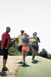 Mature man training a group of adult runners - CUF33398