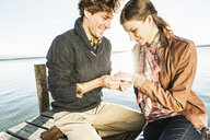 Man putting engagement ring on woman - CUF33464