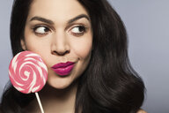 Mid adult woman holding pink lollipop - ISF14127