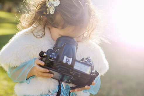 Female toddler in garden peering down into camera lens - ISF14157