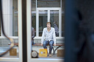 Young man sitting on train station bench - CUF33610