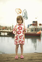 Portrait of young girl on pier with fishing nets, Southwold, Suffolk, UK - CUF33622
