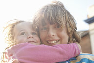 Close up portrait of boy and toddler sister hugging - CUF33631