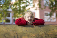 Portrait of blond little girl leaning on wooden railing - JFEF00884