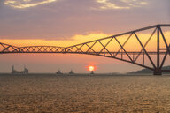 United Kingdom, Scotland, Firth of Forth, Forth Rail Bridge with tug boats underneath and Hound Point Oil Loading Marine Terminal at sunset - SMAF01045