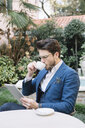 Elegant businessman drinking coffee and using tablet in a garden cafe - ALBF00538