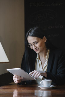 Smiling young businesswoman using tablet in a cafe - ALBF00556