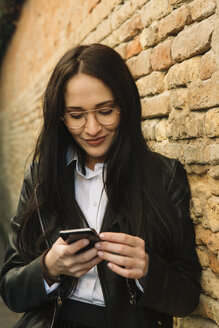 Smiling young woman using cell phone at brick wall - ALBF00568