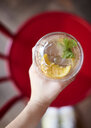 Woman's hand holding glass of lemonade, top view - ABIF00649