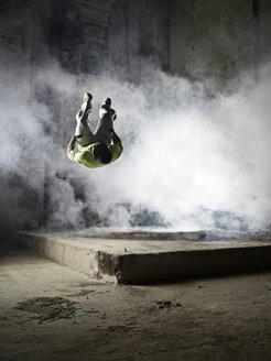 Man jumping in dust cloud during freerunning exercise - CVF00851