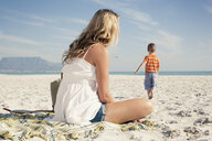 Mid adult mother watching young son play on beach, Cape Town, Western Cape, South Africa - CUF33708