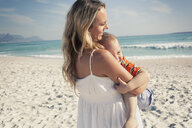Mid adult mother carrying young son on beach, Cape Town, Western Cape, South Africa - CUF33711