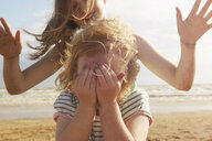 Girl covering eyes in front of sister on beach, Camber Sands, Kent, UK - CUF33720