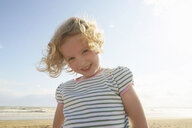 Portrait of cute girl on beach, Camber Sands, Kent, UK - CUF33723