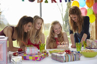 Teenage girl sharing birthday cake with friends - CUF33783